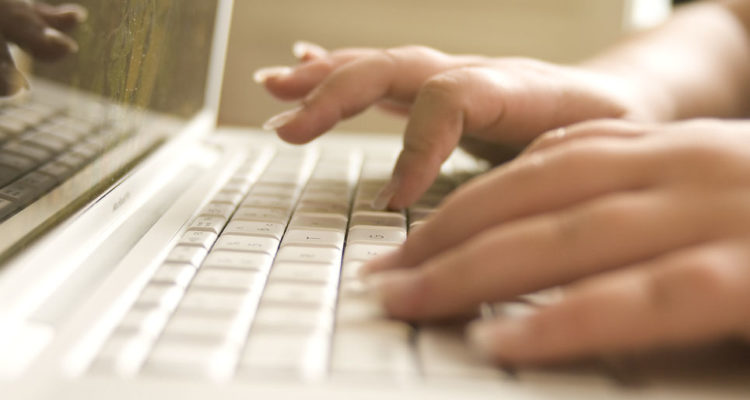 Hands typing in a laptop